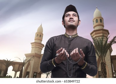 Handsome asian muslim man holding prayer beads and praying with mosque background