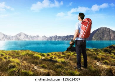 Handsome asian photograper man with backpack and camera on the mountain