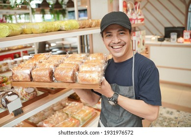 handsome asian smiling worker at the bakery shop holding a tray of bread