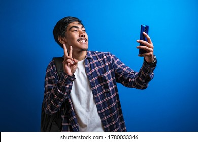 handsome asian student man with flannel shirt, taking selfie on smartphone, video calling friends via app, mobile phone messanger, smiling pleased, blue background