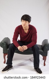 Handsome Asian teenager sitting and looking at the camera with a thoughtful expression