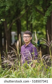 Handsome Asian young man with glasses standing behind the thick growth of grass