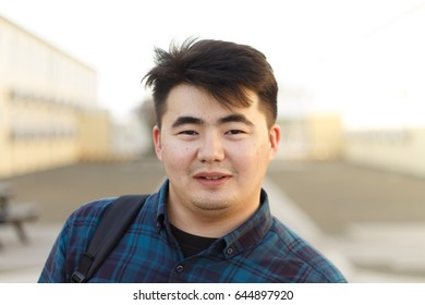 Handsome Asian young man pose on office brown containers