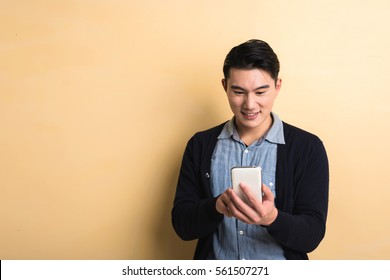 handsome Asian young man using smartphone, shot at studio yellow background