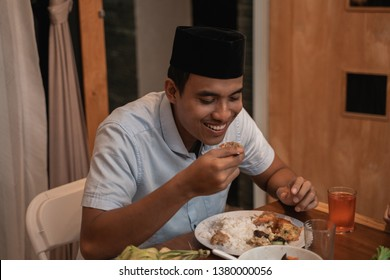 handsome asian young muslim man eating dinner with family