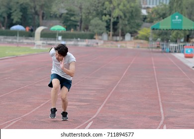Handsome athlete Asian man running on racetrack in stadium with copy space background. Healthy active lifestyle concept.