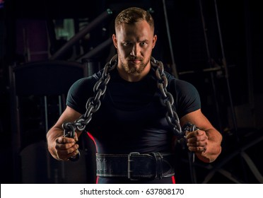 Handsome athlete with a chain around his neck stands in the gym and looks straight ahead
