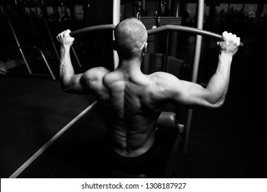 Handsome Athlete Doing Heavy Weight Exercise For Back On Machine