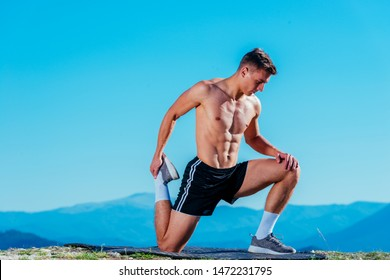 Handsome athlete ( sportsman ) stretching out and preparing for a workout on top of a mountain with an amazing view on the landscape.