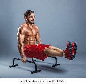 Handsome athlete working out exercise on parallel bars on a gray background