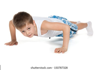 A handsome athletic boy is pushing up on the white background