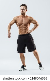Handsome athletic fitness muscular man posing on a white background in studio