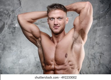 Handsome athletic fitness muscular man posing on a gray background in studio