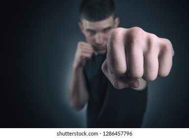 Handsome athletic man in boxing stand. Focus on fist