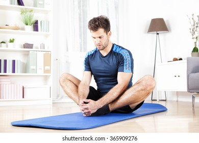 Handsome Athletic Man Doing Seated Adductor Stretch Exercise at Home