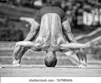 handsome Athletic man doing yoga asanas in the park