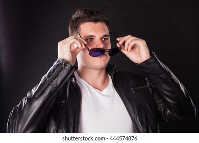 handsome athletic man athletic guy in the studio on a black background posing looking at the camera, rocker in the black leather jacket, sunglasses