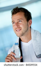 Handsome athletic man at the gym holding a bottle of water