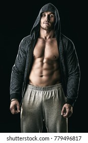 Handsome athletic man in hoodie posing over black background. Sports and bodybuilding concept. Healthy lifestyle.