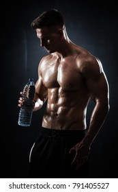 Handsome athletic man posing with bottle of water on black background