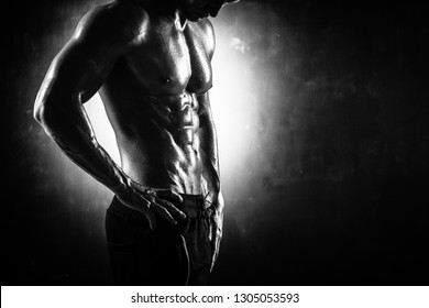 Handsome athletic man posing on black background in monochrome