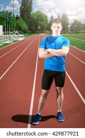Handsome athletic man posing on track field outdoor while relaxing after exercise.