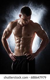 Handsome athletic man posing on black background