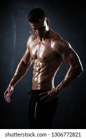 Handsome athletic man showing his trained body on dark background