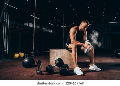 handsome athletic man sitting on cube with gym equipment around and clapping hands with talc before workout