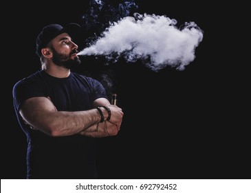 Handsome athletic man is vaping an e-cigarette. Black background. Studio shooting.