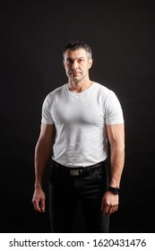 Handsome Athletic man in white blank t-shirt standing on black wall background