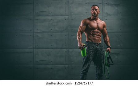 Handsome Athletic Men Holding Protein Drink Bottle and Resistance Bands. Copy Space