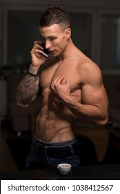 Handsome, athletic and shirtless young man in jeans near black table at home and speaking on mobile phone showing his tattoos on his stretch right arm, with smile