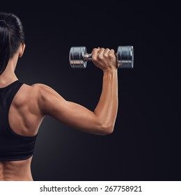 Handsome athletic woman in training pumping up muscles of the back and hands with dumbbells