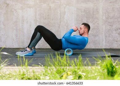 Handsome athletic young man in sportswear outfit doing exercises with abs roller