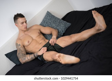 Handsome, athletic young shirtless man in Black Men's Shorts on the bed with black sheets with his legs stretching out and his arms on his head showing his muscles and tattoos