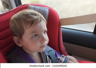 Handsome attentitive baby boy in child car seat. He is watching toons with tablet on headrest