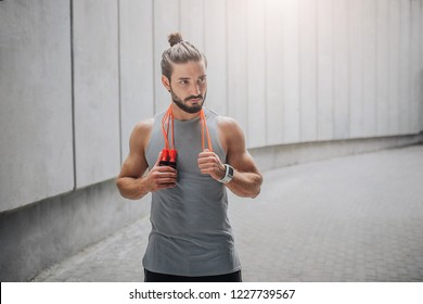 Handsome and attractive bearded guy stands and looks to right. He has orange rope around neck. Young man has rest. He stands at grey wall.