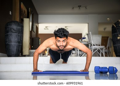 Handsome and attractive male fitness model is getting ready to do some push ups in his living room