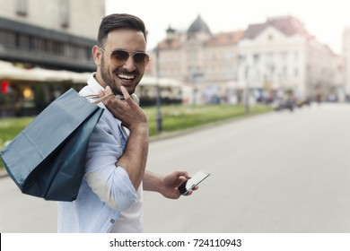 Handsome attractive man smiling shopping in the city