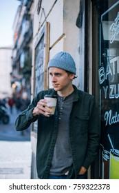 Handsome and attractive trendy hipster man, stands outside cafe or coffee shop and drinks take away or to go cup with hot tea or other winter beverage,concept big city life and autumn