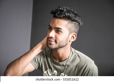 Handsome and attractive young male model with fashionable hairstyle posing for the camera
