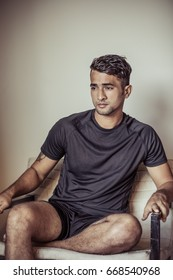 Handsome and attractive young male model with dark fashionable hair and a good face is sitting in athleisure sportswear