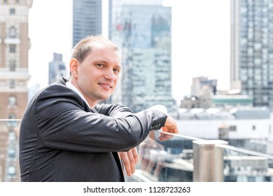 Handsome, attractive young side profile businessman closeup face portrait standing in suit, tie, looking at New York City cityscape skyline in Manhattan at skyscrapers rooftop