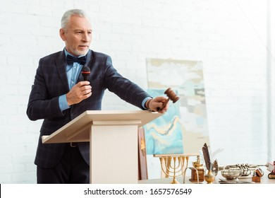 handsome auctioneer in suit talking with microphone and holding gavel during auction