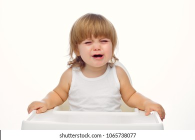 a handsome baby 1.6 years old sits in a white child's highchair.