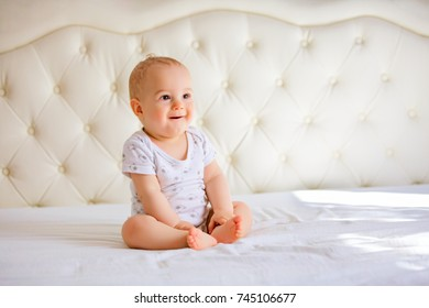 handsome baby boy in white sunny bedroom.