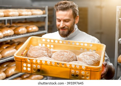 Handsome baker holding box full of freshly baked buckweat breads at the manufacturing