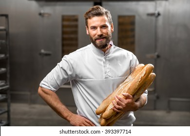 Handsome baker in uniform holding baguettes with oven on the background at the manufacturing