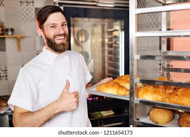Handsome baker in white uniform holding in his hands a tray full of freshly baked croissants against the background of a bakery